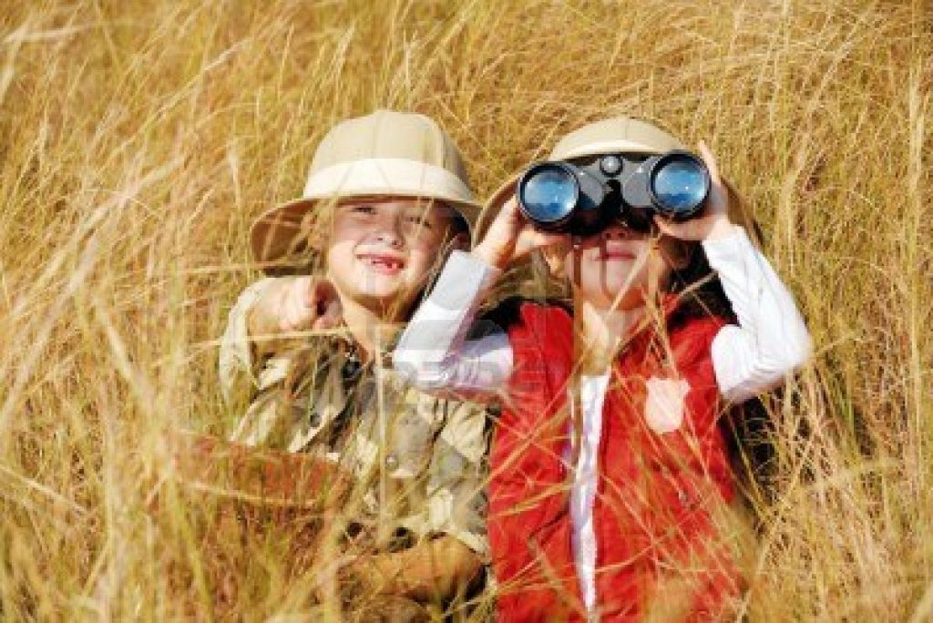 14055872-happy-young-safari-adventure-children-playing-outdoors-in-the-grass-with-binoculars-and-exploring-to